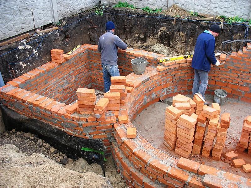 Каменщики в работе над бассейном