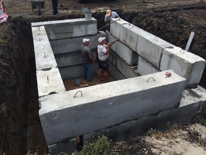 Фото 1. Монтаж бетонных блоков подвала