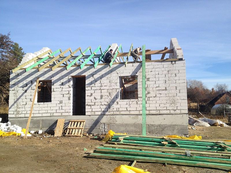 Строители выполняют монтаж деревянной стропильной системы