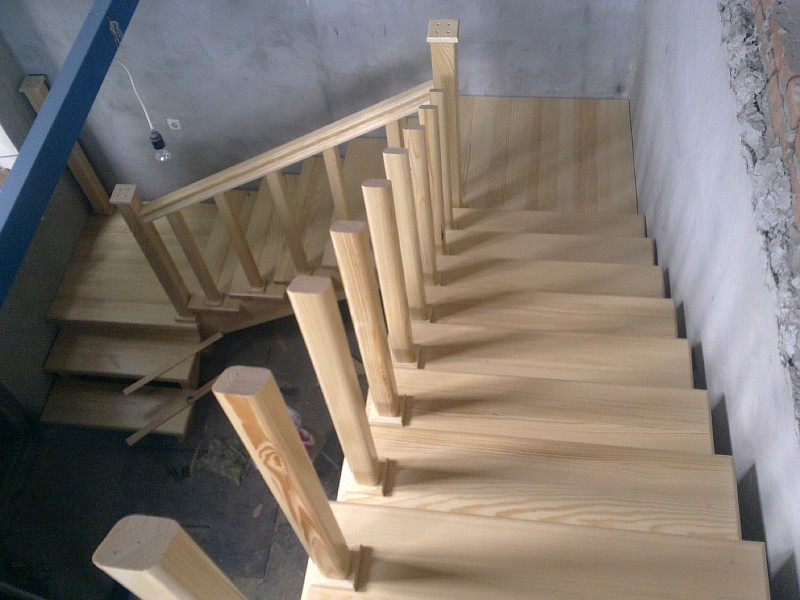 Вид сверху на трехмаршевую лестницу из сосны на этапе выполнения монтажа