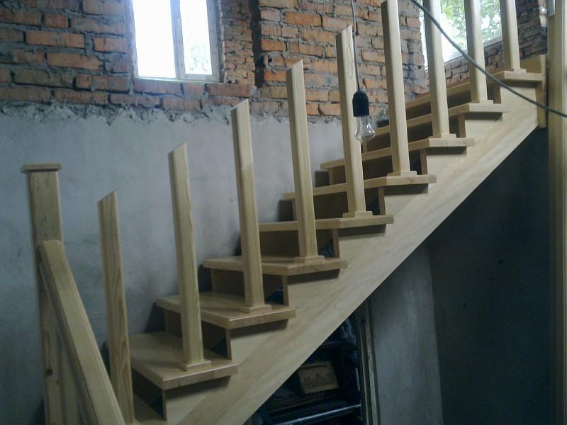 Вид сбоку на верхний марш деревянной лестницы без подступенков